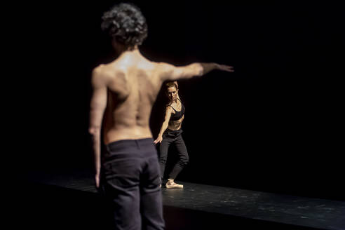 Male and femal dancer performing contemporary ballet on black stage - NGF00627