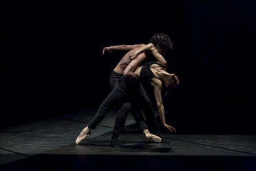 Male and femal dancer performing contemporary ballet on black stage - NGF00630