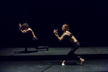 Male and femal dancer performing contemporary ballet on black stage - NGF00633
