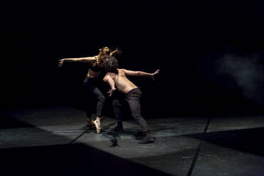 Male and femal dancer performing contemporary ballet on black stage - NGF00636