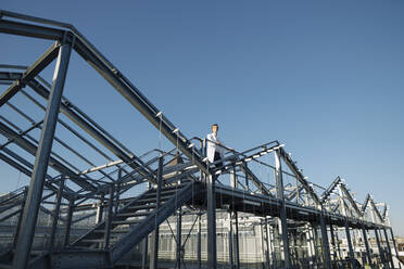 Scientist on a metal construction under blue sky - JOSEF01623