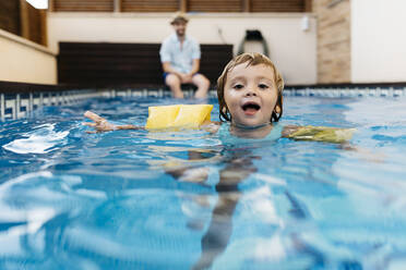 Little girl in swimming pool, her uncle on poolside - JRFF04696