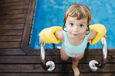 Little girl with armbands at ladder of swimming pool - JRFF04699