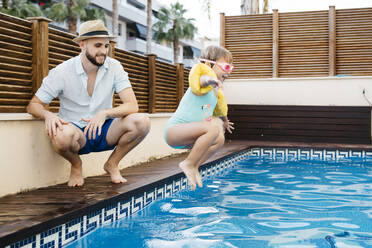 Little girl jumping into water, her uncle at poolside - JRFF04705