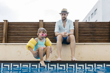 Little girl jumping into water, her uncle at poolside - JRFF04708