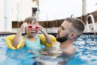 Little girl with her uncle in swimming pool - JRFF04711