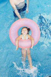 Little girl with floating tire and her uncle in swimming pool - JRFF04717
