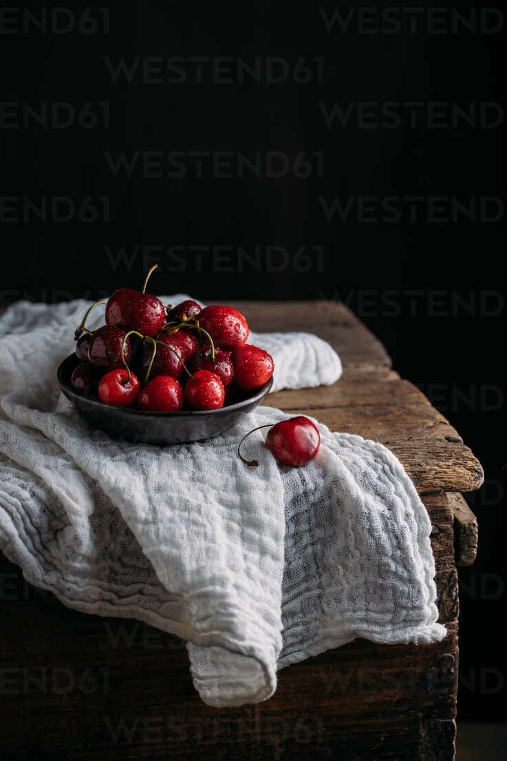 Bow Full Of Fresh Cherries On Wooden Table And White Muslin Fabric Against Dark Background Adsf13996