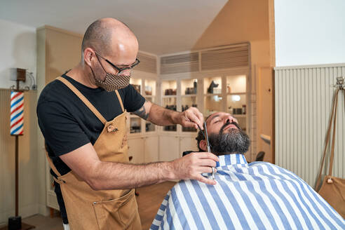 Barber in protective mask standing next to male consumer lying on comfortable hairdressing chair and cutting beard with scissors in modern salon - ADSF14020