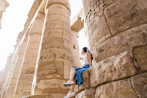 Low angle full length faceless stylish female traveler sitting on stone construction and admiring historic architecture in ancient ruined heritage building with hieroglyphs on weathered columns - ADSF14116