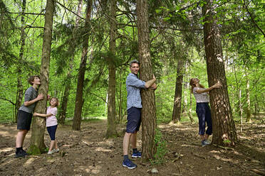 Family embracing tree while standing in forest - ECPF01031