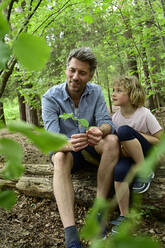 Smiling father talking with daughter while sitting on log in forest - ECPF01037