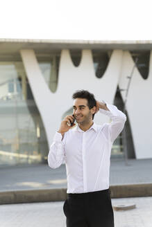 Handsome businessman with hand in hair talking over smart phone while standing against built structure - AFVF07154
