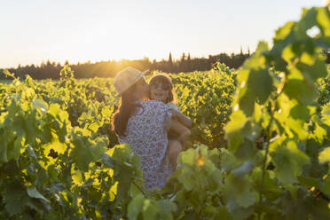 Mother holding her daughter in a vineyard at sunset in Provence, France - GEMF04117