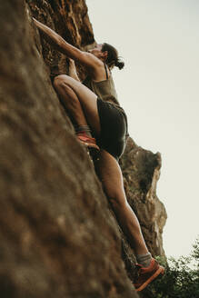 Determinant woman climbing rock mountain in forest - DMGF00127