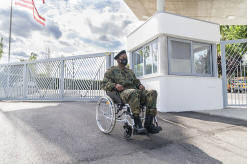Army soldier with protective face mask sitting on wheelchair against cloudy sky - MTBF00654