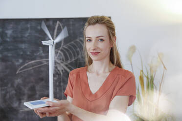 Portrait of confident woman in office holding wind turbine model - FKF03817