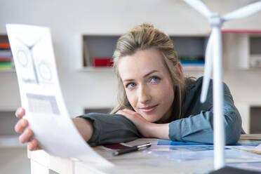 Portrait of woman leaning on desk in office with paper and wind turbine model - FKF03841