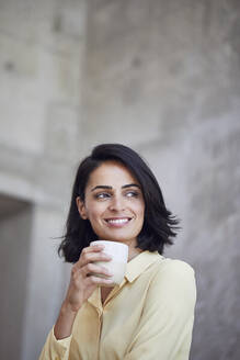 Close-up of smiling female entrepreneur holding coffee cup against wall in office - MCF01245
