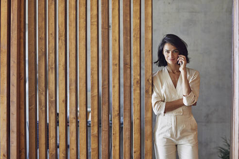 Businesswoman talking over smart phone while standing by wooden door in office - MCF01251