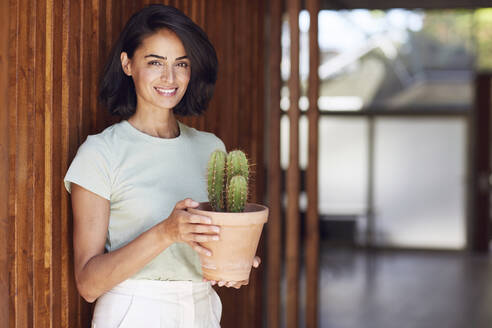 Smiling female entrepreneur holding cactus plant while standing by wooden wall in office - MCF01266