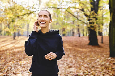 Young female jogger with earphones in autumn forest - BSZF01686