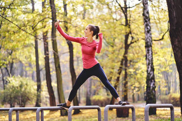 Young female jogger taking a selfie on bicycle stand in autumn forest - BSZF01692