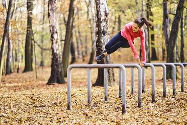 Young female jogger jumping over bicycle stands in autumn forest - BSZF01695
