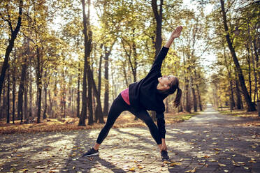 Young female jogger stretching her leg in autumn forest - BSZF01704