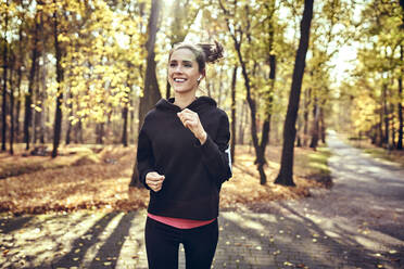 Young woman jogging in autumn forest - BSZF01707