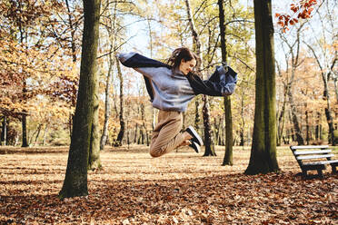 Young woman jumping in autumn forest - BSZF01713