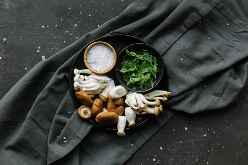 Top view of bowl with assorted mushrooms placed with parsley and salt on napkin in kitchen - ADSF14413