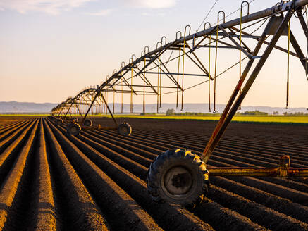 Irrigation equipment kept on ploughed field during sunset - NOF00127