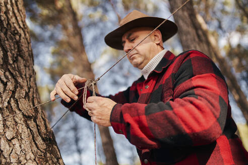 Bushcrafter tying rope to tree bark in forest - SASF00039