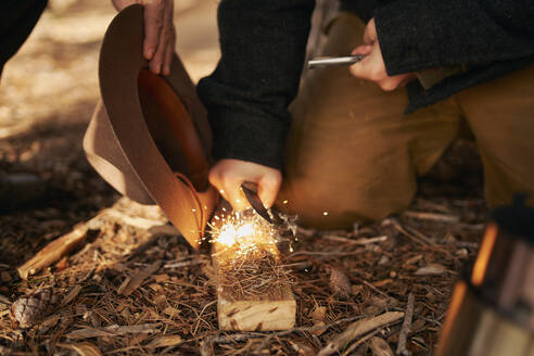 Midsection of bushcrafters enlighten fire in forest - SASF00045