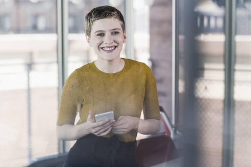 Portrait of smiling businesswoman in office holding mobile phone - UUF21131