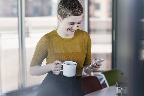 Smiling businesswoman in office holding coffee mug and mobile phone - UUF21134