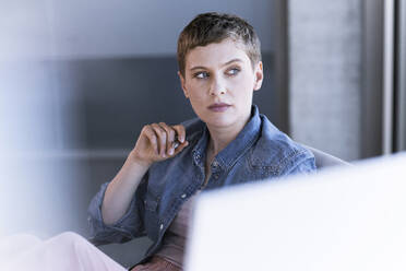 Businesswoman thinking at desk in office - UUF21176