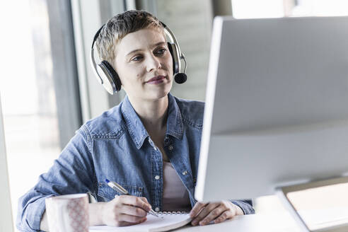 Businesswoman wearing headset at desk in office taking notes - UUF21182