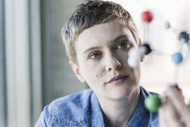 Woman looking at molecule model - UUF21185