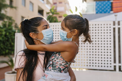 Mother holding daughter wearing mask while standing outdoors - EGAF00681