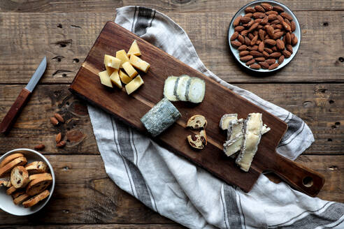 Sweet croutons with raisins and plate with almonds placed on wooden table near board with various cut cheese - ADSF14463