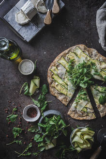 From above top view of pizza with greenery slices of squash on table with spices olive oil cheese for vegetarian dinner - ADSF14547