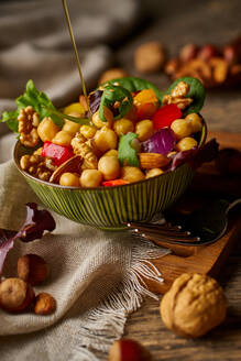 From above appetizing colorful cut vegetable mix with chickpeas and walnuts on wooden background - ADSF14646