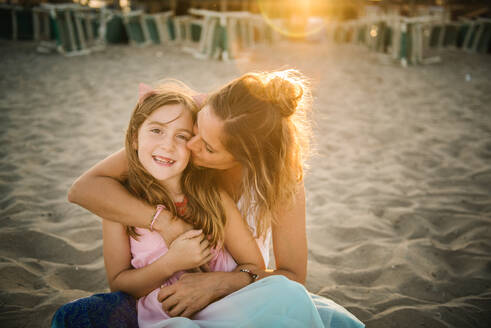 Adult woman kissing beautiful girl embracing with love on sandy beach in sunset light - ADSF14670