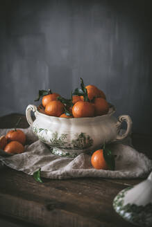 Sophisticated still life with ripe orange tangerines with green leaves in deep white bowl on table on gray background - ADSF14697