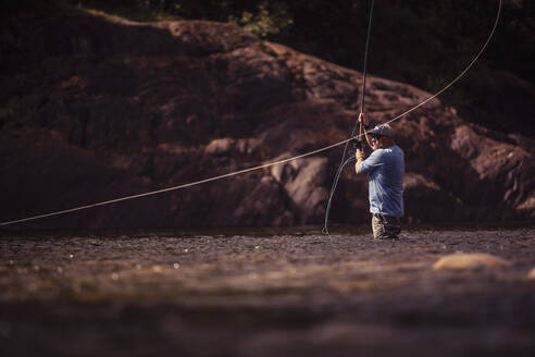 Fly fisherman casting with two handed rod in river - DHEF00348