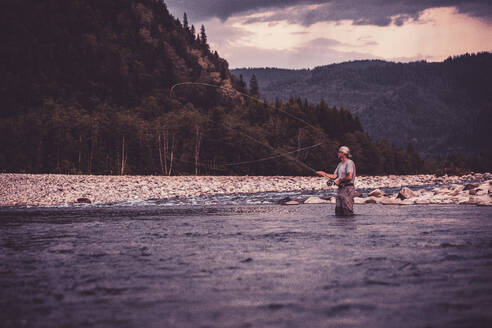 Fly fisherman casting with fishing rod while standing in river - DHEF00354