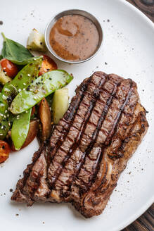 From above top view of grilled beef steak with basil and vegetable serving on plate with BBQ sauce - ADSF14719