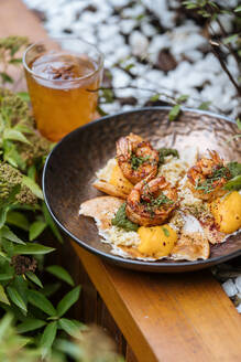 From above tasty fresh fried eggs with shrimps covered by herbs in pan on wooden table in garden - ADSF14725